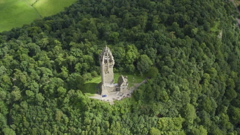 AX109_100.0000080F - Aerial stock photo of The iconic Wallace Monument surrounded by trees on Abbey Craig, Scotland