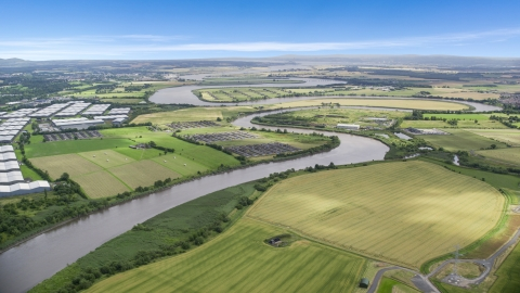 AX109_102.0000000F - Aerial stock photo of The River Forth near warehouses and green farm fields in Fallin, Scotland