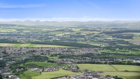 AX109_166.0000053F - Aerial stock photo of Farmland and a Scottish village, Bonnybridge, Scotland