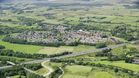 AX109_172.0000093F - Aerial stock photo of Farm fields and highway M80 by rural village homes, Bonnybridge, Scotland