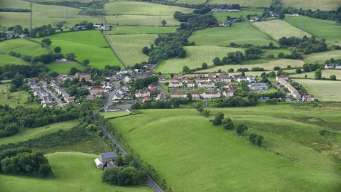 AX110_233.0000280F - Aerial stock photo of Rural homes surrounded by farmland in Cumbernauld, Scotland