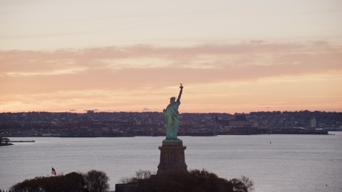 AX118_041.0000196F - Aerial stock photo of Statue of Liberty with a view of Brooklyn at sunrise, New York