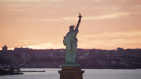 AX118_042.0000000F - Aerial stock photo of Statue of Liberty with a view of Brooklyn at sunrise, New York