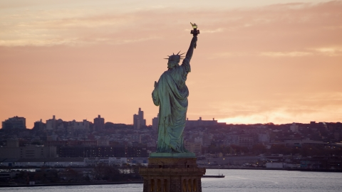 AX118_042.0000079F - Aerial stock photo of Back of the Statue of Liberty at sunrise, New York