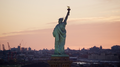 AX118_042.0000234F - Aerial stock photo of Behind the Statue of Liberty at sunrise, New York