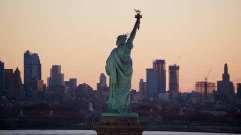 AX118_043.0000107F - Aerial stock photo of Statue of Liberty and Brooklyn skyline at sunrise, New York