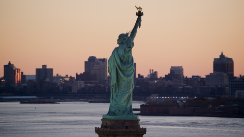 AX118_044.0000000F - Aerial stock photo of Statue of Liberty, and Brooklyn across the harbor at sunrise, New York