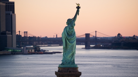 AX118_044.0000159F - Aerial stock photo of Statue of Liberty at sunrise, Brooklyn Bridge in the background, New York