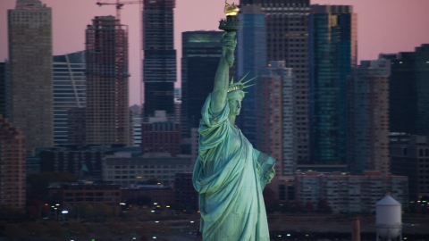 AX118_046.0000299F - Aerial stock photo of The Statue of Liberty at sunrise, New York