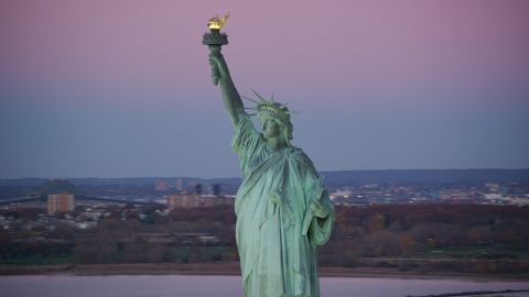 AX118_050.0000000F - Aerial stock photo of Statue of Liberty with purple sky at sunrise, New York