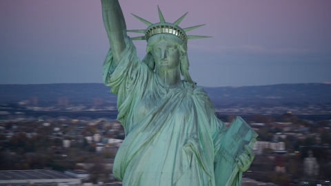 AX118_059.0000153F - Aerial stock photo of Statue of Liberty at sunrise, purple sky overhead, New York