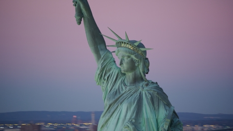 AX118_060.0000000F - Aerial stock photo of Profile of the Statue of Liberty at sunrise, New York