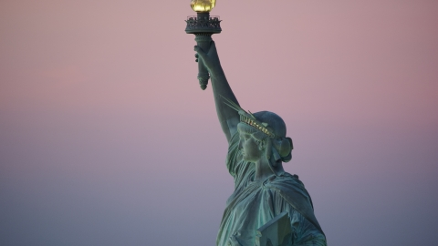 AX118_060.0000227F - Aerial stock photo of The Statue of Liberty's profile at sunrise, New York