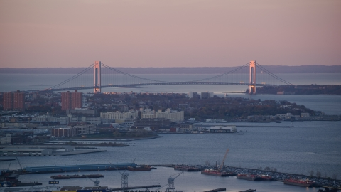 AX118_061.0000092F - Aerial stock photo of Verrazano-Narrows Bridge and waterfront apartment buildings at sunrise, New York City