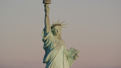 AX118_107.0000082F - Aerial stock photo of The front of the Statue of Liberty at sunrise in New York