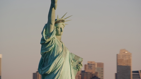 AX118_108.0000070F - Aerial stock photo of Profile of the Statue of Liberty at sunrise in New York