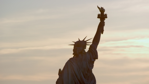 AX118_111.0000000F - Aerial stock photo of Back of the Statue of Liberty at sunrise in New York