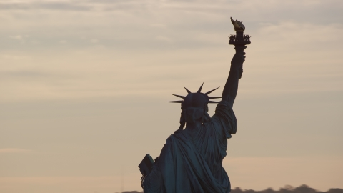 AX118_111.0000148F - Aerial stock photo of The back of the Statue of Liberty at sunrise in New York