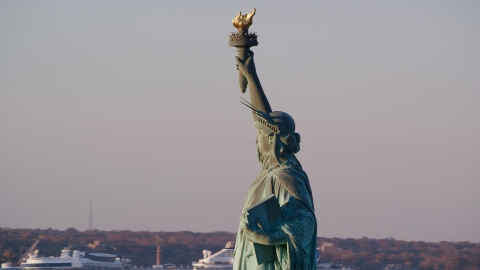 AX118_114.0000066F - Aerial stock photo of Left side profile of the Statue of Liberty at sunrise in New York