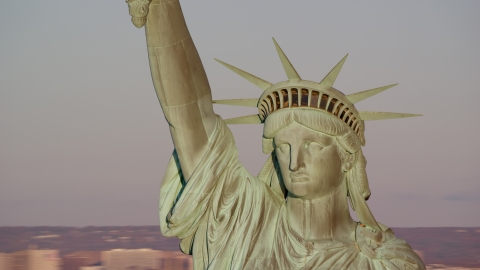 AX118_116.0000128F - Aerial stock photo of Close-up of the Statue of Liberty at sunrise in New York