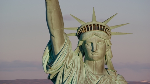 AX118_116.0000231F - Aerial stock photo of A close-up of the Statue of Liberty at sunrise in New York
