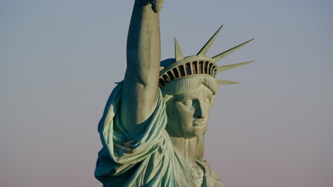 AX118_117.0000113F - Aerial stock photo of Close-up profile of the Statue of Liberty at sunrise in New York