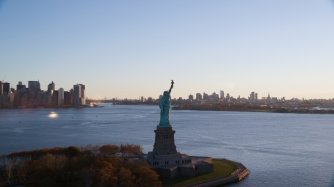 AX118_118.0000000F - Aerial stock photo of Statue of Liberty with Brooklyn in the background at sunrise in New York