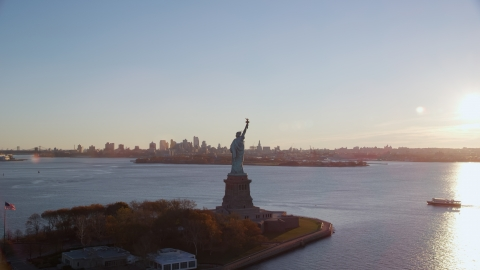 AX118_118.0000187F - Aerial stock photo of Statue of Liberty and Brooklyn across the harbor at sunrise in New York