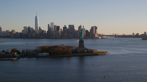 AX118_122.0000000F - Aerial stock photo of Statue of Liberty and Lower Manhattan skyline at sunrise in New York