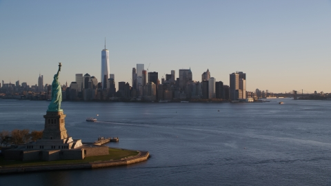 AX118_122.0000202F - Aerial stock photo of The Statue of Liberty and Lower Manhattan skyline at sunrise in New York