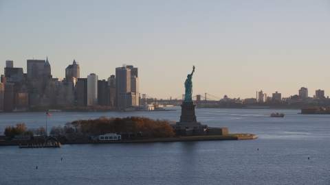 AX118_132.0000000F - Aerial stock photo of Statue of Liberty and Lower Manhattan skyscrapers at sunrise in New York City