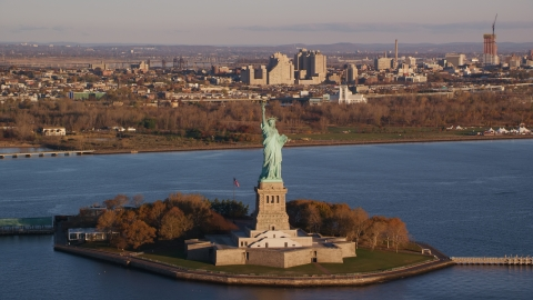 AX118_144.0000175F - Aerial stock photo of Statue of Liberty at sunrise in New York, with Jersey City in the background
