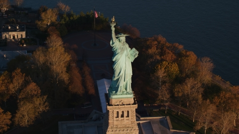 AX118_146.0000077F - Aerial stock photo of Statue of Liberty and autumn trees at sunrise in New York