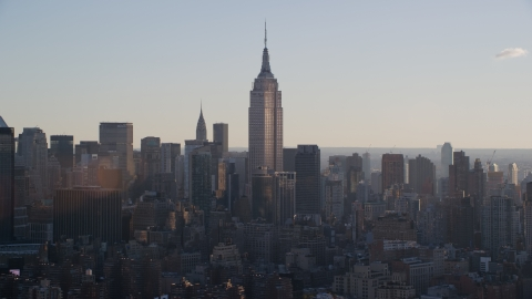 AX118_162.0000089F - Aerial stock photo of Empire State Building at sunrise in New York City
