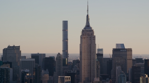 AX118_166.0000205F - Aerial stock photo of Empire State Building and 432 Park Avenue at sunrise in Midtown Manhattan, New York City