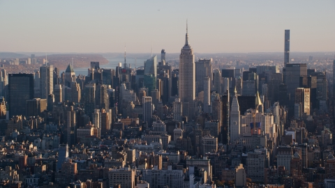 AX118_169.0000092F - Aerial stock photo of Empire State Building and Midtown Manhattan buildings at sunrise in New York City