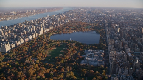 AX118_192.0000000F - Aerial stock photo of Central Park with autumn leaves and The Met at sunrise in New York City