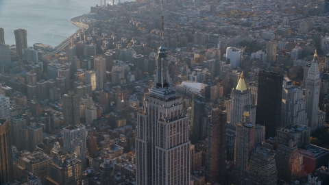 AX118_204.0000082F - Aerial stock photo of The spire on top of the Empire State Building at sunrise in Midtown Manhattan, New York City