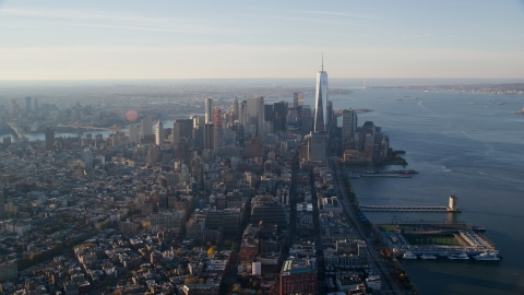 AX118_208.0000101F - Aerial stock photo of Lower Manhattan and piers on the Hudson at sunrise in New York City