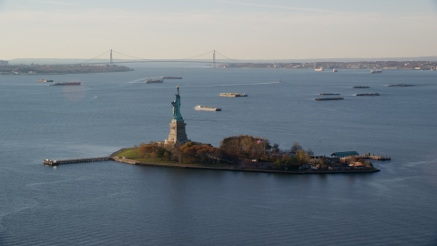 AX118_216.0000172F - Aerial stock photo of Statue of Liberty and barges in New York Bay at sunrise in New York