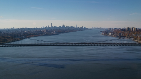 AX119_047.0000192F - Aerial stock photo of George Washington Bridge, Hudson River, and the Midtown skyline in Autumn, New York City
