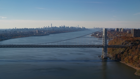 AX119_049.0000046F - Aerial stock photo of Midtown skyline behind George Washington Bridge, Hudson River in Autumn, New York City