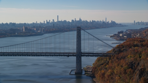 AX119_050.0000022F - Aerial stock photo of Midtown skyline behind the George Washington Bridge and the Hudson River in Autumn, New York City