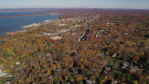 AX119_112.0000105F - Aerial stock photo of Upscale homes and small riverfront towns in autumn, Briarcliff Manor and Ossining, New York