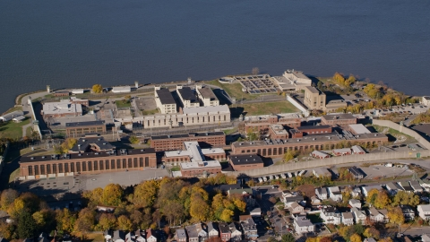 AX119_114.0000314F - Aerial stock photo of Sing Sing Prison by the Hudson River in Autumn, Ossining, New York