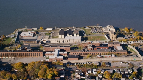 AX119_115.0000090F - Aerial stock photo of Sing Sing Prison beside the Hudson River in Autumn, Ossining, New York