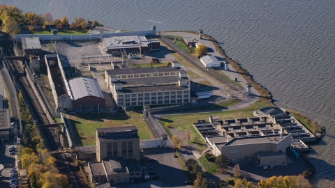 AX119_118.0000080F - Aerial stock photo of Buildings at Sing Sing Correctional Facility in Autumn, Ossining, New York