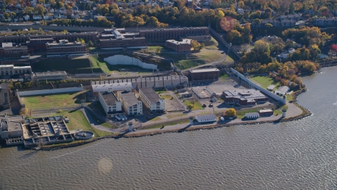 AX119_121.0000063F - Aerial stock photo of Sing Sing Prison by the Hudson River in Autumn, Ossining, New York