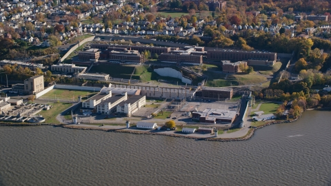 AX119_122.0000128F - Aerial stock photo of Sing Sing Prison by the Hudson River in Autumn, Ossining, New York