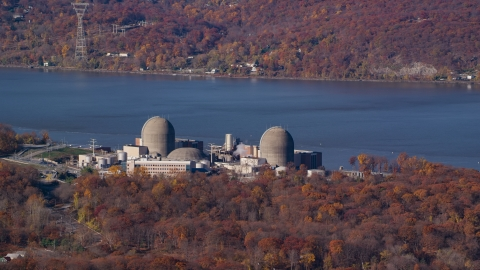 AX119_144.0000113F - Aerial stock photo of The Indian Point Energy Center nuclear power plant in Autumn, Buchanan, New York